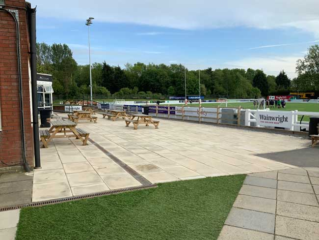 Terrace with picnic benches overlooking rugby pitch